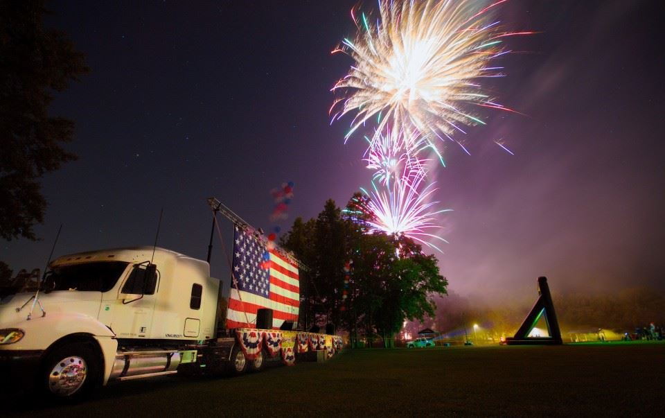 White 18 wheeler cab with American Flag hanging above truck bed with 3 white fireworks in sequencial