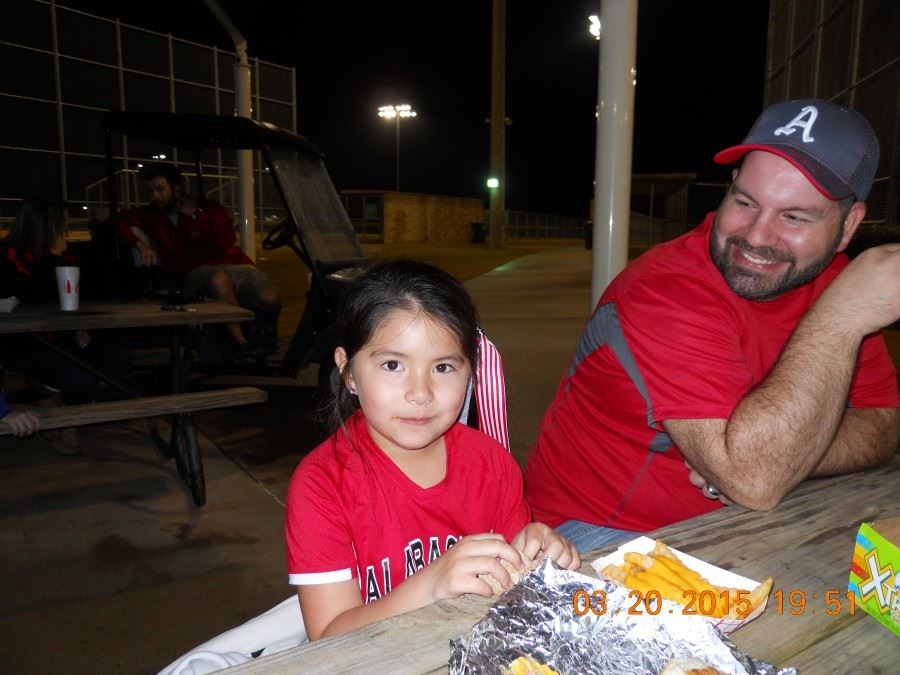 Child Eats With Her Father at a Game